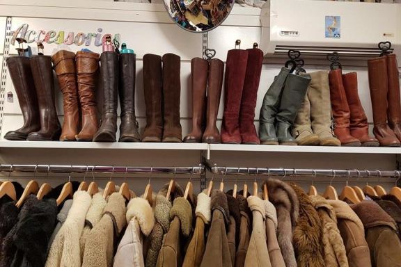 ladies boots along a shelf above a rail of winter coats