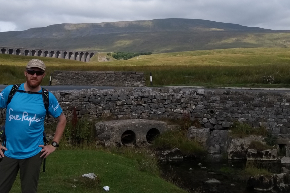 Trekker in a Sue Ryder top looks at the camera with a hill and viaduct behind him.