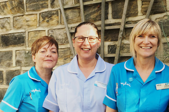 Sue Ryder Wheatfields Hospice day therapy nurses smiling against a brick wall