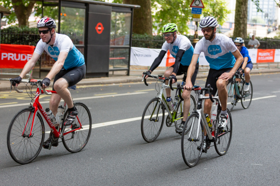 Three smiling cyclists in Sue Ryder tops head past a bus stop on their way to finishing the 2019 Prudential RideLondon