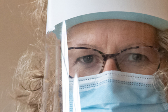 A Sue Ryder Nurse in a face mask and face shield