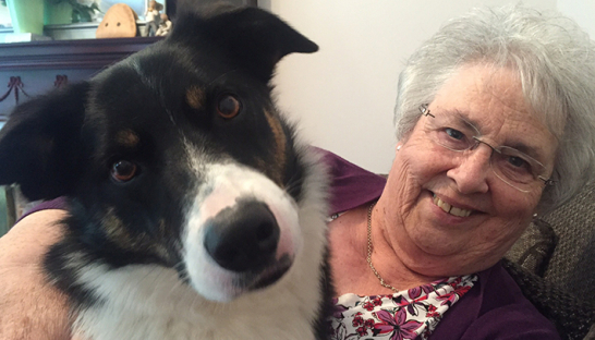 Therapy dog Mac gives Jude's mum a cuddle during their rounds