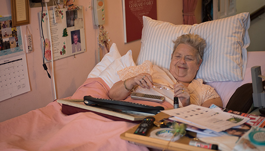 Neurological patient Gill tucked up in bed