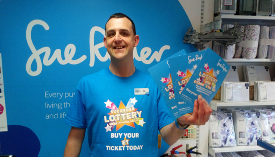 A shop worker promotes the Sue Ryder lottery and lucky dips