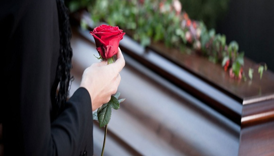 Image of a person with a rose stood next to a coffin