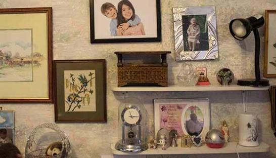 Image of a bedroom with photos on the walls - Sue Ryder advice and support