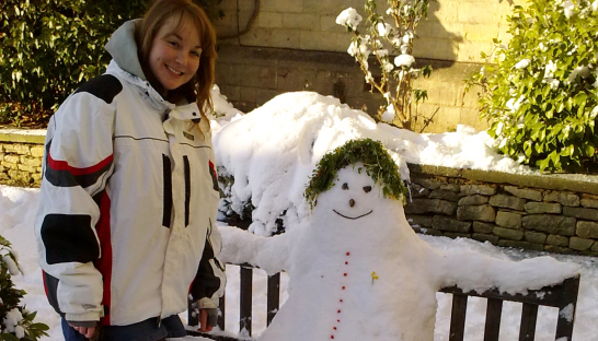 Jamie with the snowman she built in the grounds of Leckhampton Court Hospice
