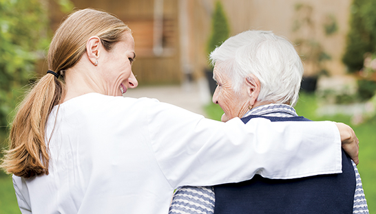 A Sue Ryder volunteer with her arm around a patient