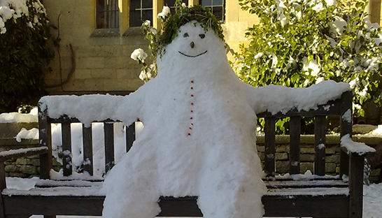Smiling snowman sitting on a bench at Leckhampton