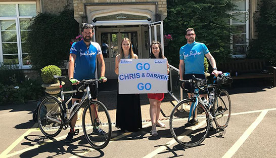 "Chris, Darren and their bikes next to hospice staff with a ""Go Chris & Darren go!"" sign."