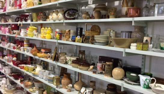 shelves of bric-a-brac including vases, bowls and jugs