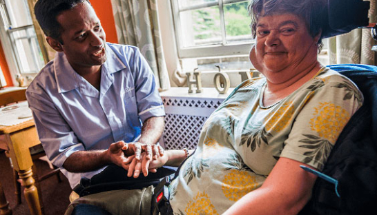 Image of a Sue Ryder male Healthcare Assistant with a neurological resident at The Chantry