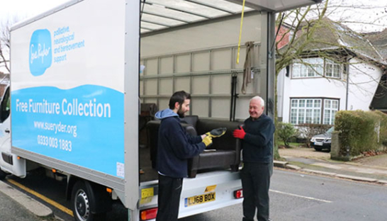 Photo of a Sue Ryder charity free furniture collection van and two delivery men