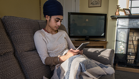 A girl wrapped in a blanket browsing the Online Community on her tablet 546