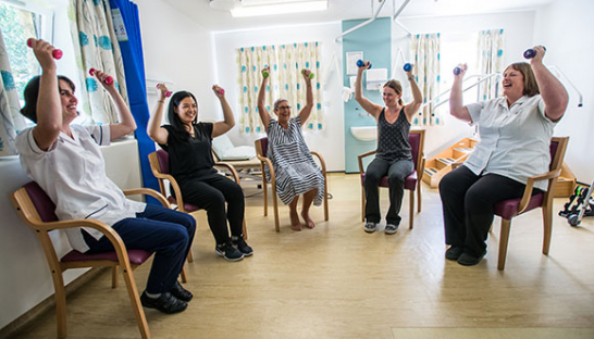 Photo of a physiotherapy exercise group lifting arm weights while sat in chairs at Sue Ryder Leckhampton Court Hospice
