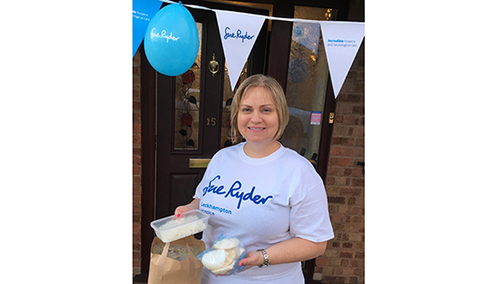 Gill at one of her fundraisers holding tubs of food