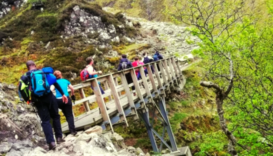 Walkers head across a bridge on Ben Nevis