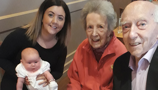 A mum and a baby meet older homecare patients at an intergenerational afternoon tea