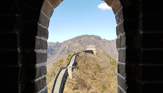 A Sue Ryder supporter looking through an arch of the Great Wall of China onto further steps