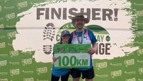 Kate with her 100km Ultramarathon finisher sign