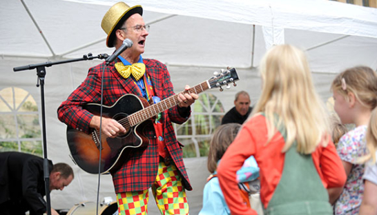 A performer playing guitar to children at last year's Leckhampton Autumn Fayre