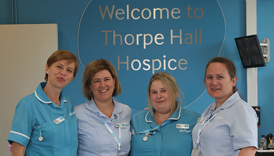 Thorpe Hall Hospice at Home nursing team under the Welcome to Thorpe Hall sign
