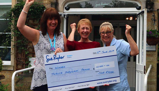 Image of Sue Ryder team with a big lottery winner's cheque
