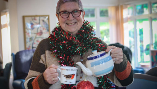 Sue Ryder volunteer, Paulette Vallois, with a tinsel scarf & tea cup