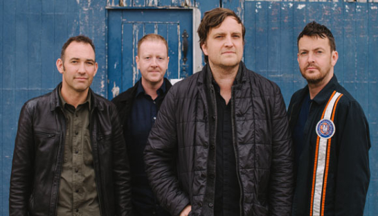 The band Starsailor in front of a blue wooden shed.