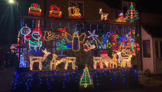 A house covered in bright, colourful Christmas lights