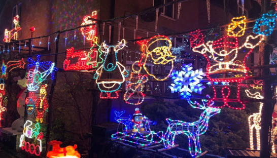 A family's house covered in colourful Christmas lights