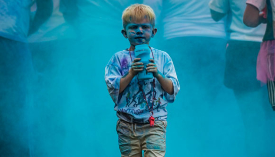 A boy covered in blue paint after the PaintRush race event.