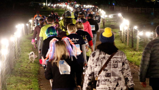 People walking through a lighted pathway at night for the Starlight Hike 2020