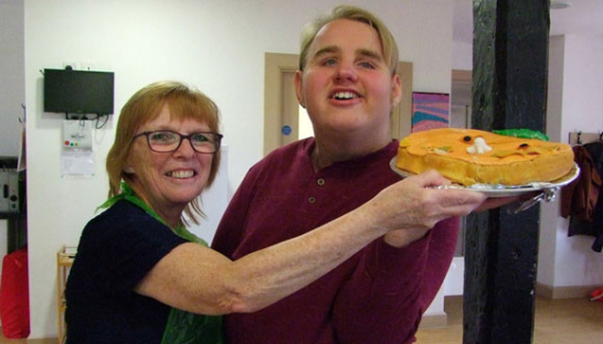 A carer and young person both holding their cake creation