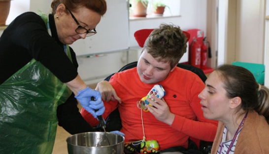 Carers and a young person making a cake