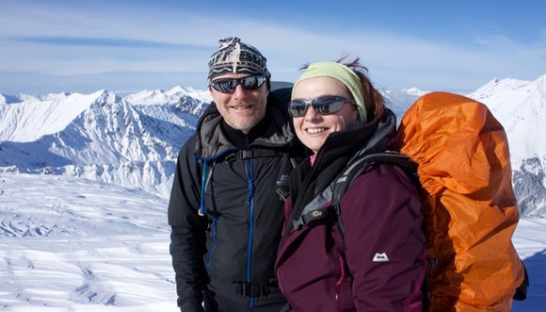 Jane and her husband Ian hiking through snowy mountains.