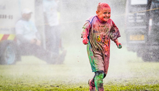 A child covered in paint during the PaintRush Manorlands 2020 event