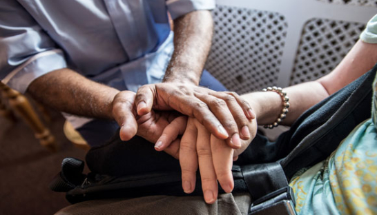 A Sue Ryder Nurse and patient holding hands.