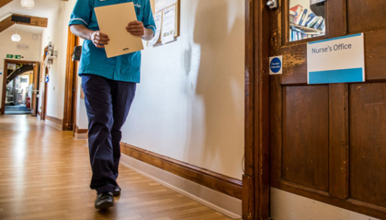 A Sue Ryder Nurse walking down the hall at a hospice