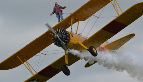 Jean wing-walking on top of a plane.