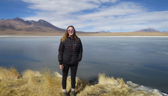 Image of Sue Ryder volunteer, Niamh, standing at a lake beside a mountain range