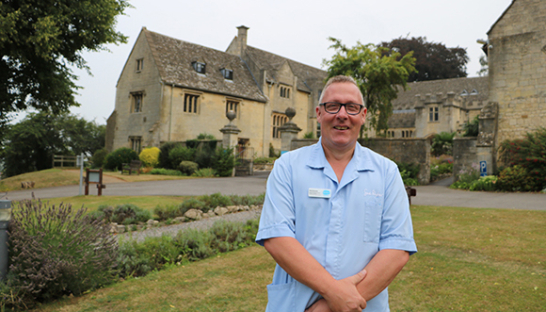 Neil, Senior Nursing Assistant at Leckhampton, in front of the hospice
