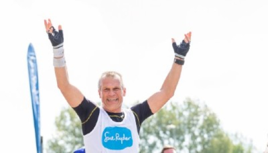 A Sue Ryder runner holding his hands up and smiling during an event