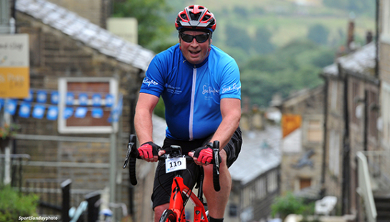 A Sue Ryder team cyclist riding up a hill during a race