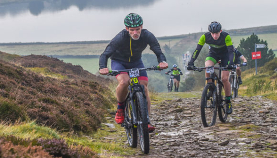 Mountain bikers racing up the hill on a muddy track