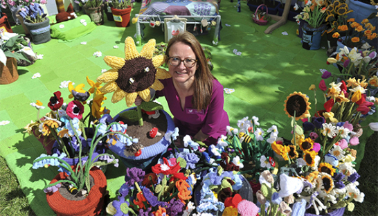 Clare Young in the Work of Heart Garden, surrounded by her flower creations.