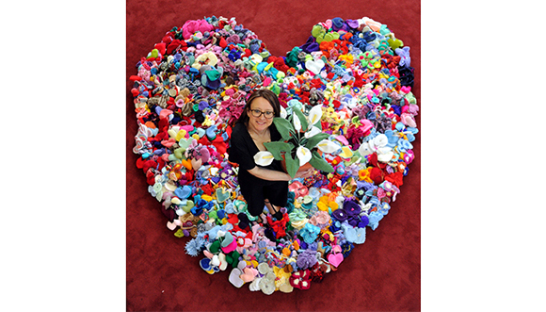 Clare Young, surrounded by a giant heart formed from knitted and crochet hearts sent to her.