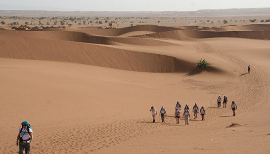 A group of people walking across the sand in the desert.