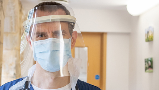 A Sue Ryder doctor in a protective face mask and face shield