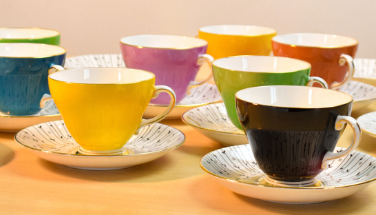 A set of different coloured teacups with saucers